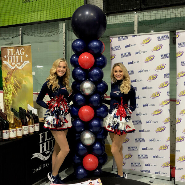 Patriots cheerleaders with one of our balloon columns at a NH expo.