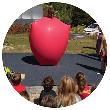Wayne performing giant climb inside balloon stunt at an outdoor magic show.
