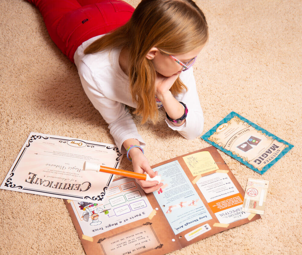 Girl on floor with Discover Magic course materials.