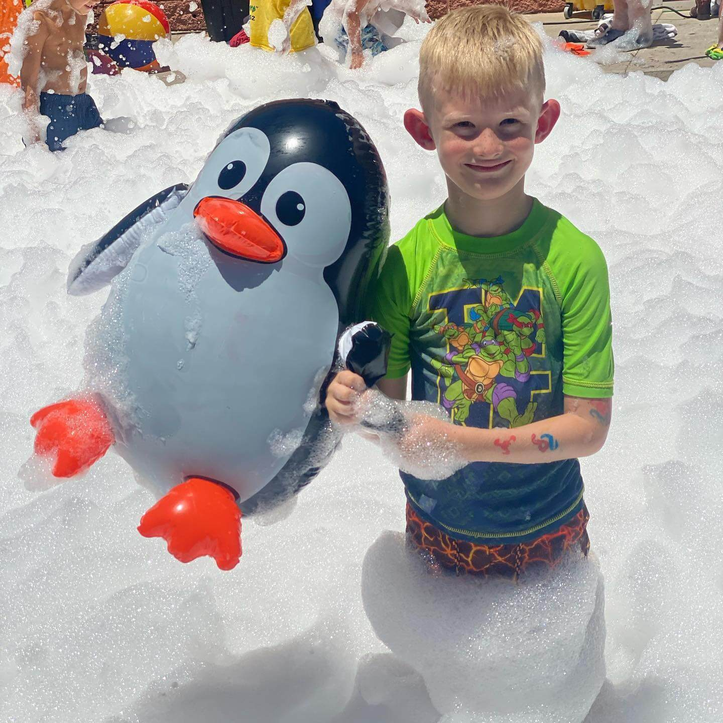Boy with inflatable penguin playing outside in a pile of foam.