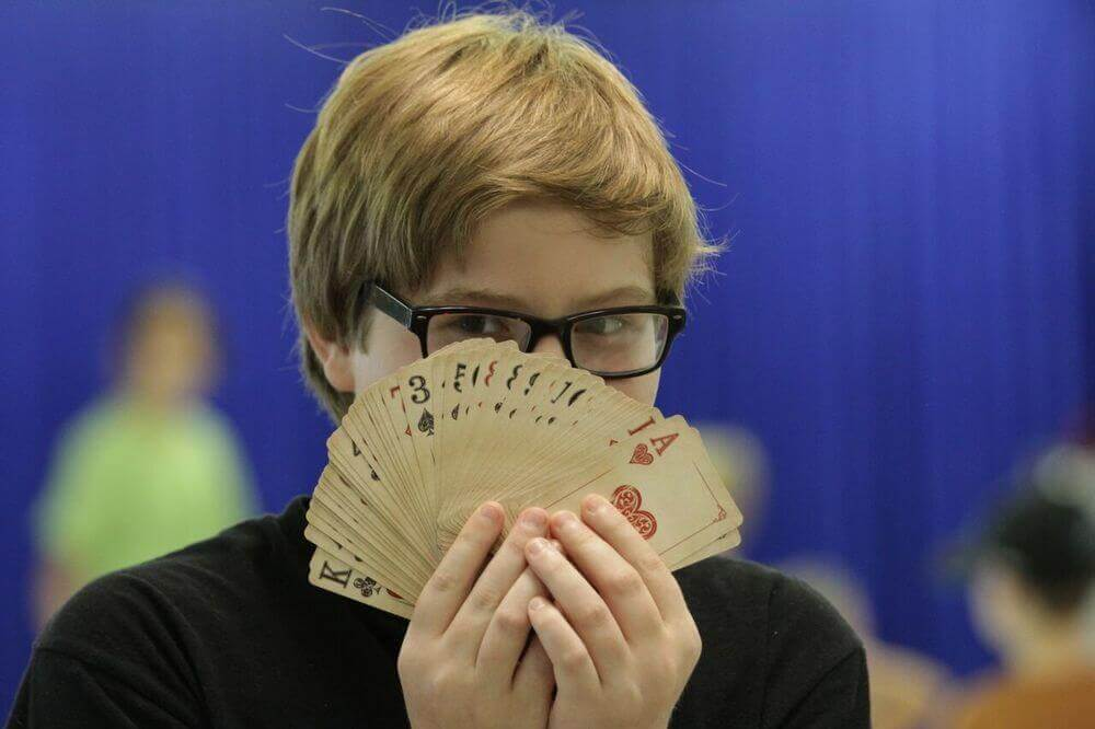 Boy looking over a fan of playing cards.