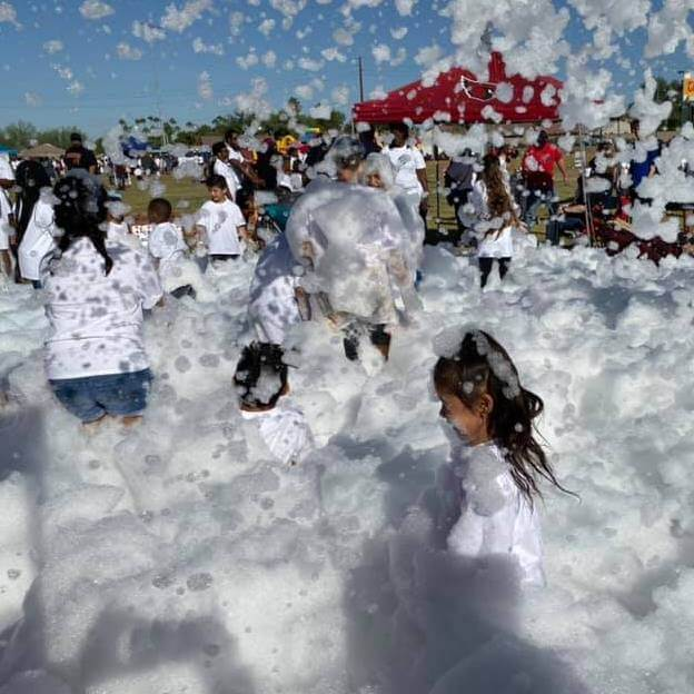 Group of kids playing outside in a pile of foam.