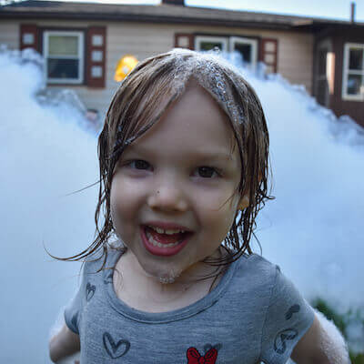 Little girl smiling in front of a pile of foam.