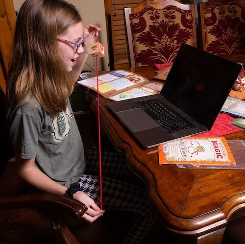A young girl showing off a magic trick during an online course.