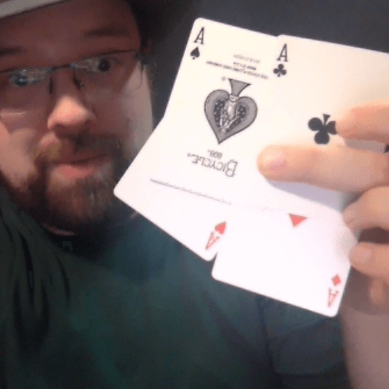 Wayne holding up four ace playing cards