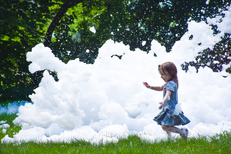 A young girl running through a pile of foam outside.