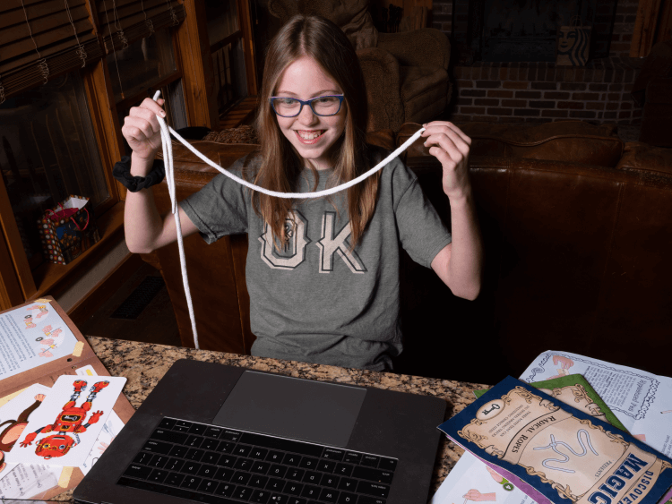 A girl learning magic at home with Discover Magic showing off a rope trick.