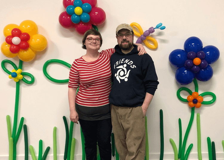 Wayne and Kali in front of a spring themed balloon photo backdrop.