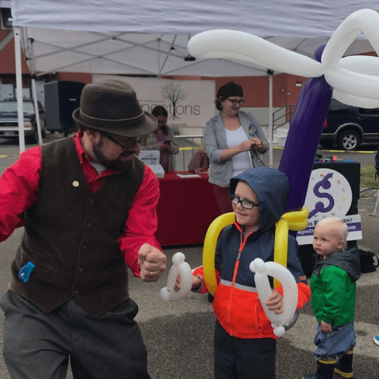 Wayne and a kid having fun with a balloon helicopter backpack at the Westival in Portsmouth, NH.