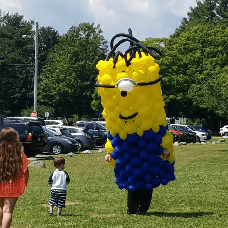 7 foot tall minion balloon sculpture outside at a two year old's birthday.