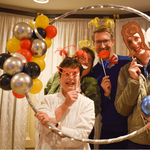 A group of adults having fun with a hand held balloon photo frame.