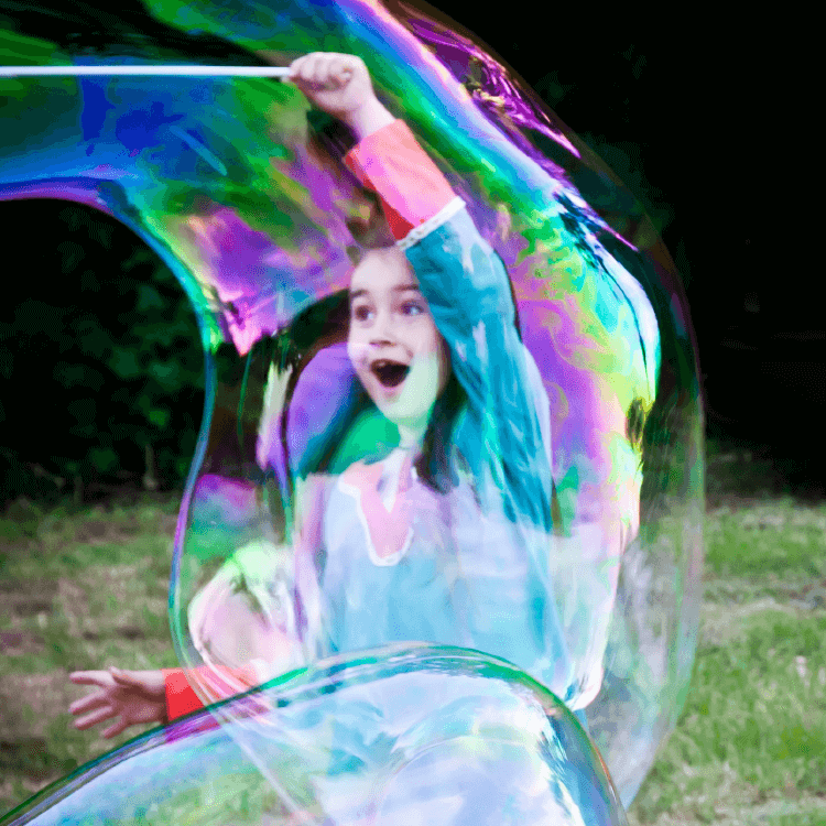 A girl with large bubbles outside.