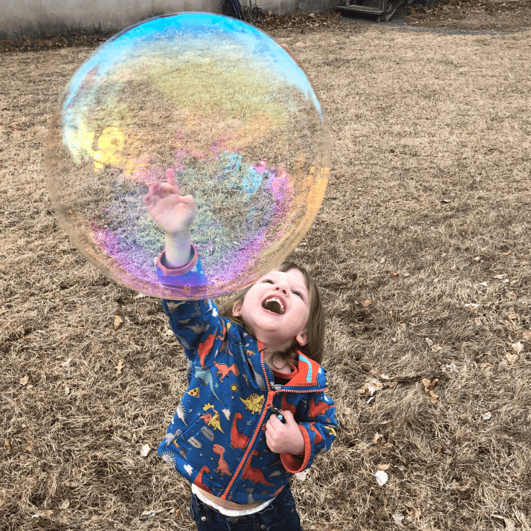 Little girl smiling with a large bubbles outside.