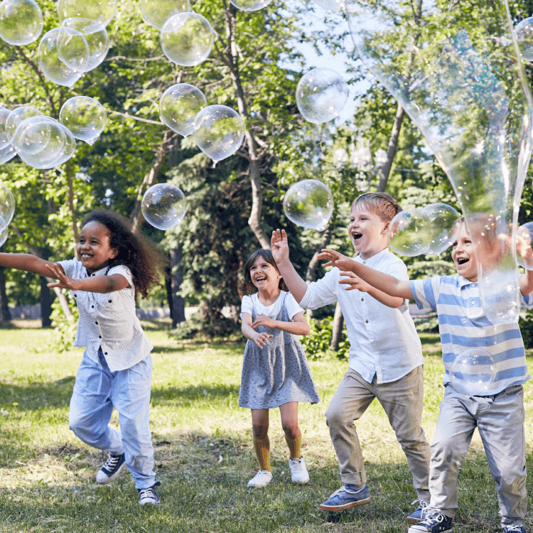 A group of kids playing with bubbles outside on a summer day.