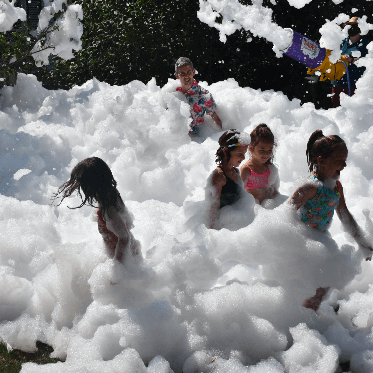 A group of kids laughing and having fun outside in foam.