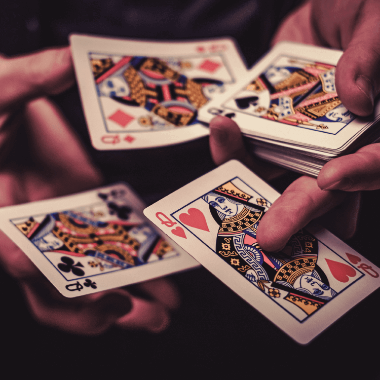 Four queen playing cards in hands.