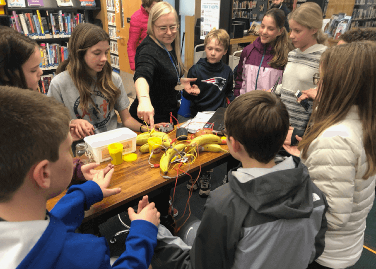 Participants interacting with Makey Makey microcontrollers at a Seacoast library.