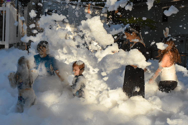 Kids and adults playing in the foam at a backyard party.