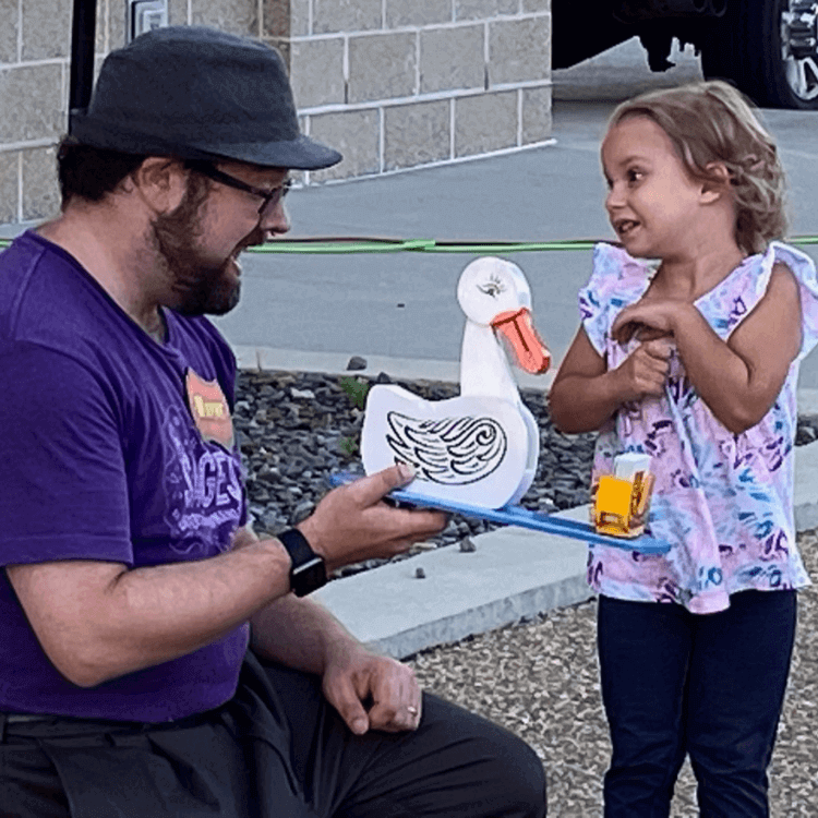 Wayne and Quincy the duck have a laugh with a little girl during a magic show.